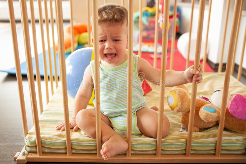Sad crying cute baby looking through the wooden bars of his crib or playpen indoors in the nursery.  royalty free stock photography