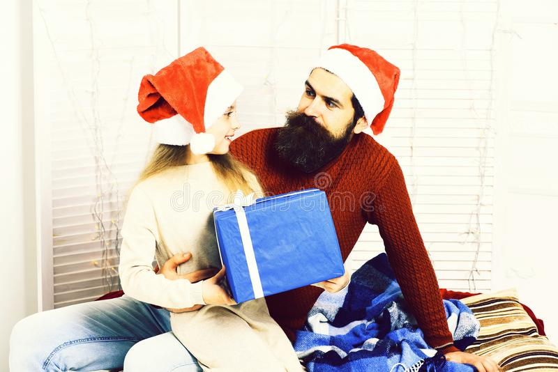 Santa man with blonde girl n beige dress sitting on knees of handsome bearded man. royalty free stock images