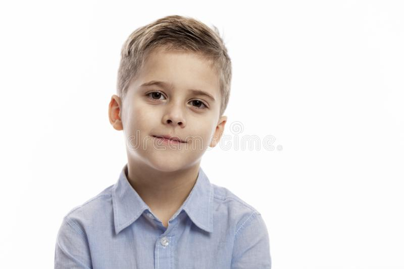 Cute smiling boy in a blue shirt is looking at the camera. White background. Close-up royalty free stock image