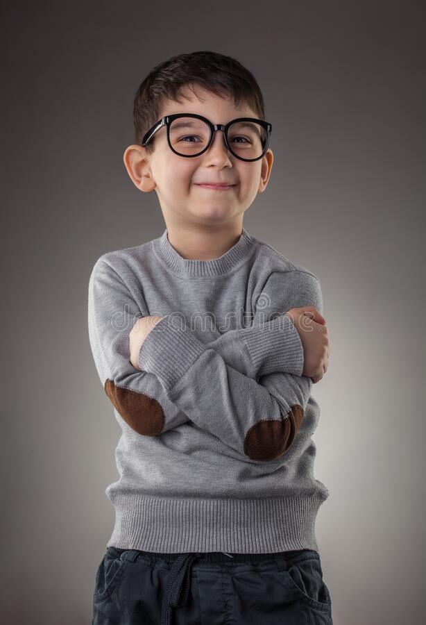 Cute smiling boy in glasses on gray background stock images