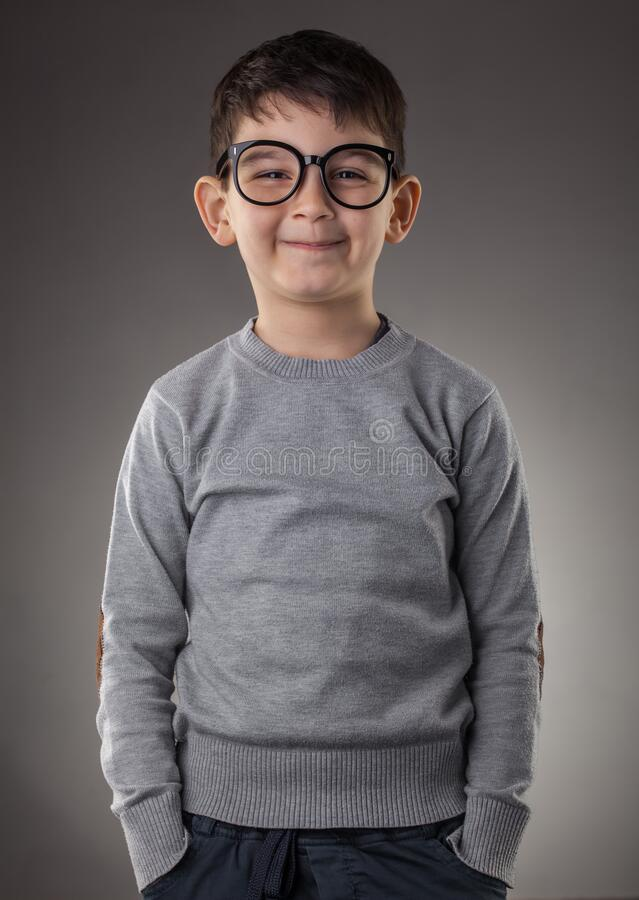 Cute smiling boy in glasses on gray background stock image