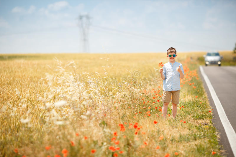 Cute smiling boy hitchhiking along lonely road. And holding bouquet of poppies royalty free stock photography