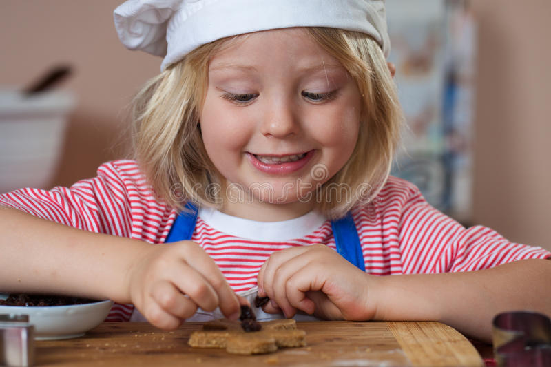 Cute smiling boy putting raisins on gingerbread stock photo