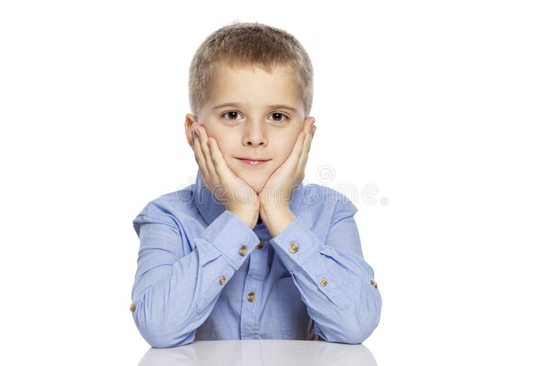 Cute smiling boy sitting at the table, propped up his head with his hands. Isolated on a white background stock image