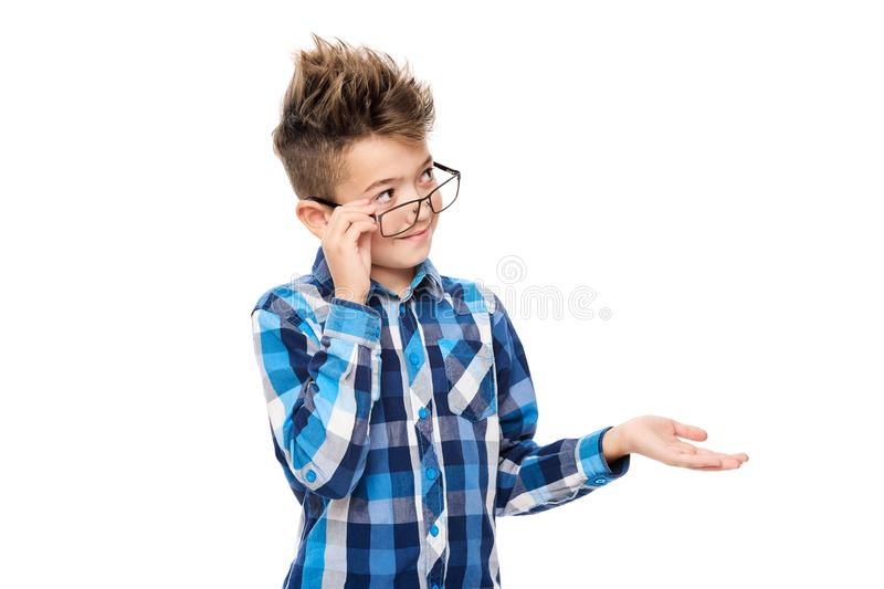 Cute smiling boy wearing reading glasses and pointing with hand to one side studio portrait on white background. stock images
