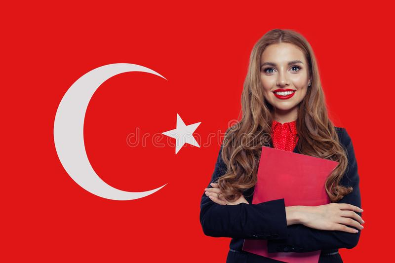Cute smiling brunette girl student with book against Turkish flag background. Study in Turkey stock images