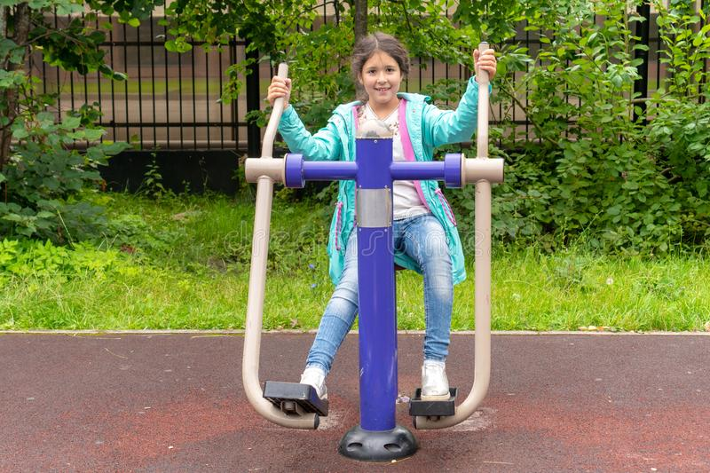 Cute smiling caucasian little girl sitting on trainer equipment outdoor sunset workout. Little girl doing exercises at the royalty free stock photo