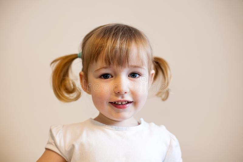 Cute smiling child girl with two pigtails and quiff stock image