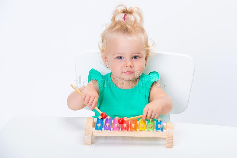 Cute smiling child little blonde baby girl playing with musical toy xylophone isolated on white background royalty free stock images