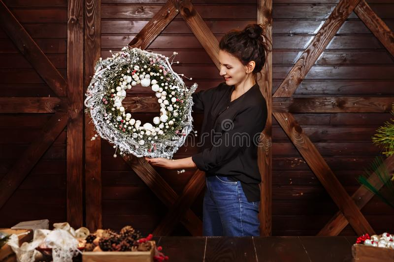Cute smiling designer showing Christmas Evergreen Tree Wreath. Young woman holding christmas wreath. Christmas wreath on stock images