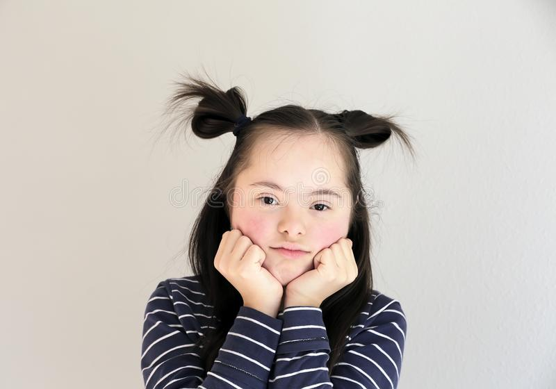 Cute smiling down syndrome girl on the grey background stock photos