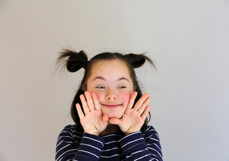 Cute smiling down syndrome girl on the grey background royalty free stock image