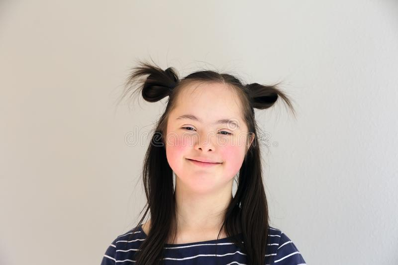 Cute smiling down syndrome girl on the grey background stock photography