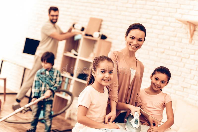 Cute Smiling Family Cleaning and Ironing Clothes. Mother with Daughters Ironing Clothes and Washing at Home. Cleaning Day Concept. Kids Helping House Chores stock images