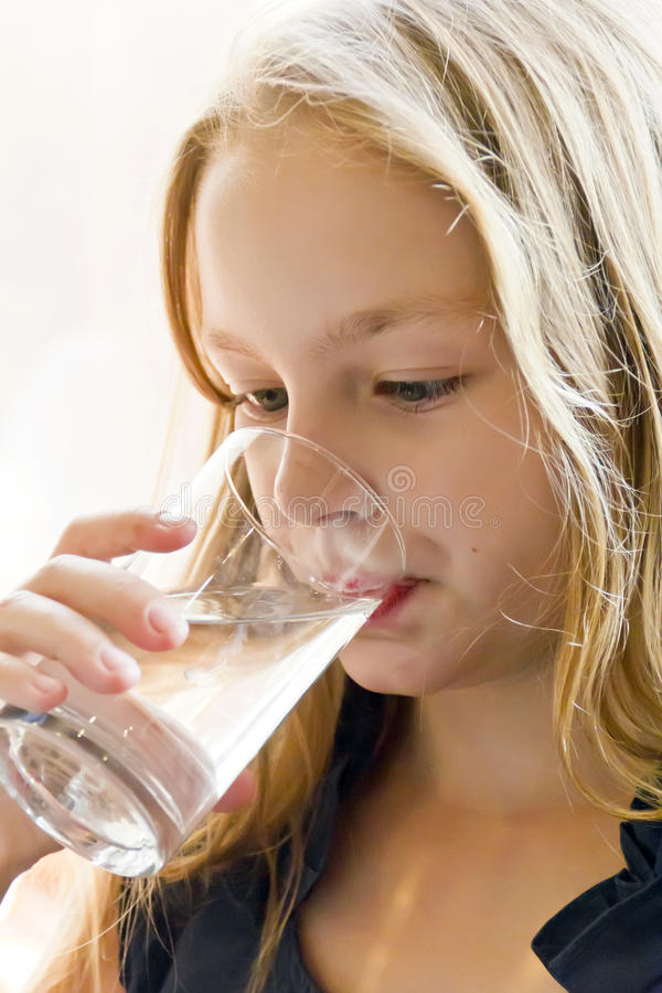 Cute smiling girl with blond hair. Cute girl with blond hair are drinking water royalty free stock photography