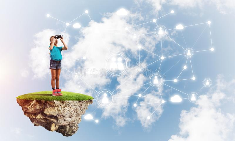 Concept of careless happy childhood with girl looking in binoculars stock photos