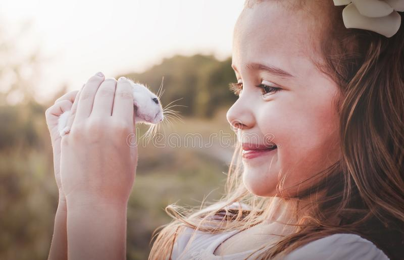 Cute smiling girl holding white hamster - Retro look royalty free stock images