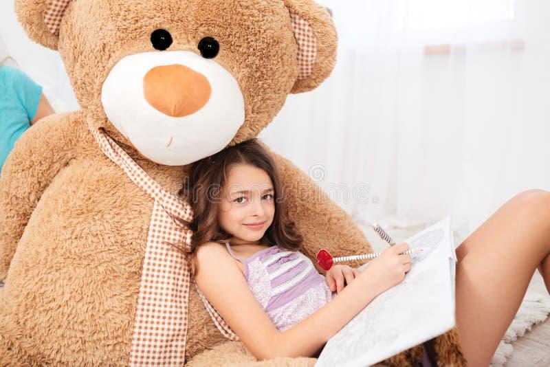 Cute smiling girl lying on big plush bear and drawing royalty free stock photo