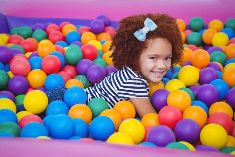 Cute smiling girl in sponge ball pool stock images