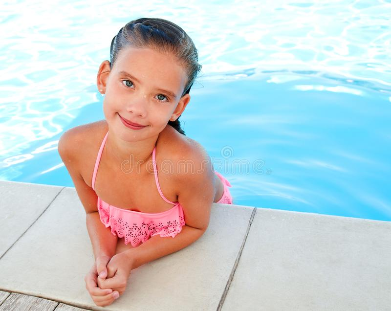 Cute smiling happy little girl child in swimming pool. In summer day royalty free stock images