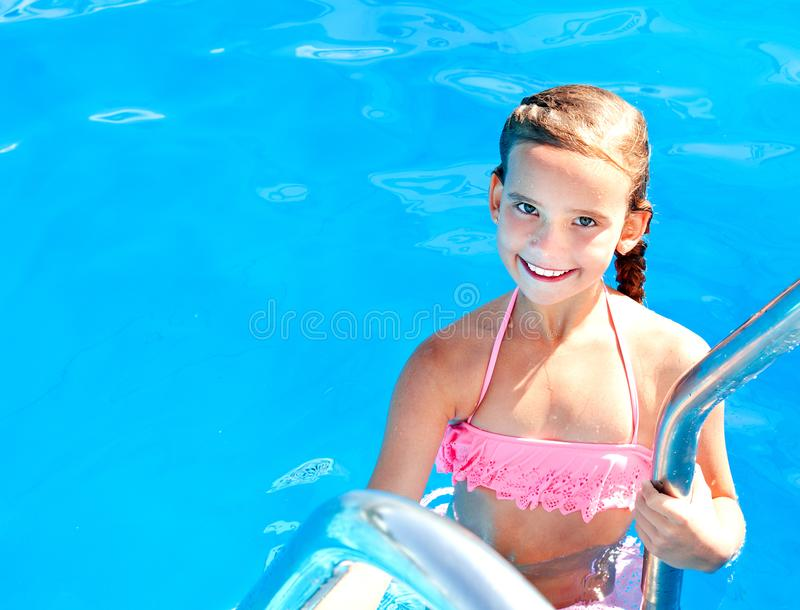 Cute smiling happy little girl child in swimming pool. In summer day stock image
