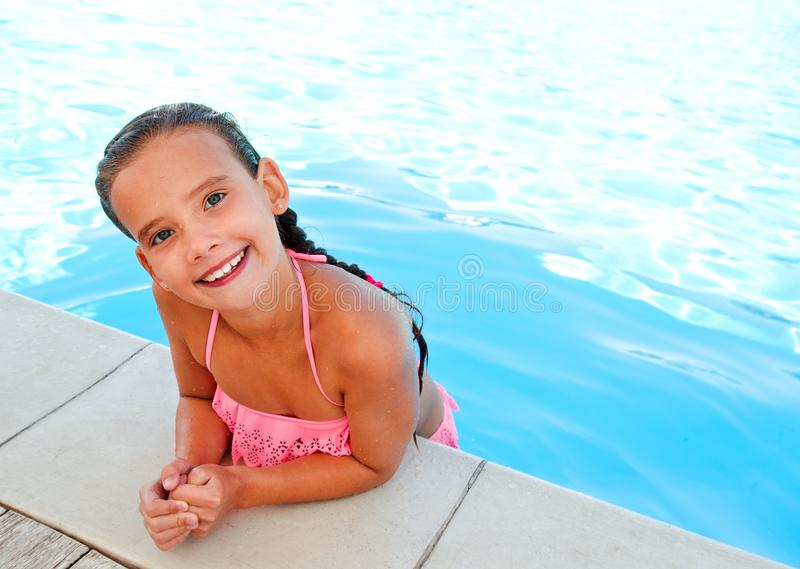 Cute smiling happy little girl child in swimming pool. In summer day royalty free stock image