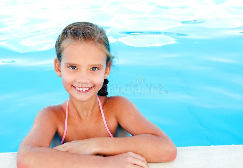 Cute smiling happy little girl child in swimming pool. In summer day stock images