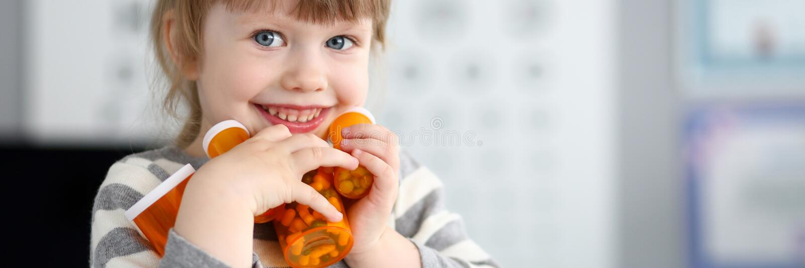 Cute smiling happy little girl grab pile of bottles with tablets stock photo