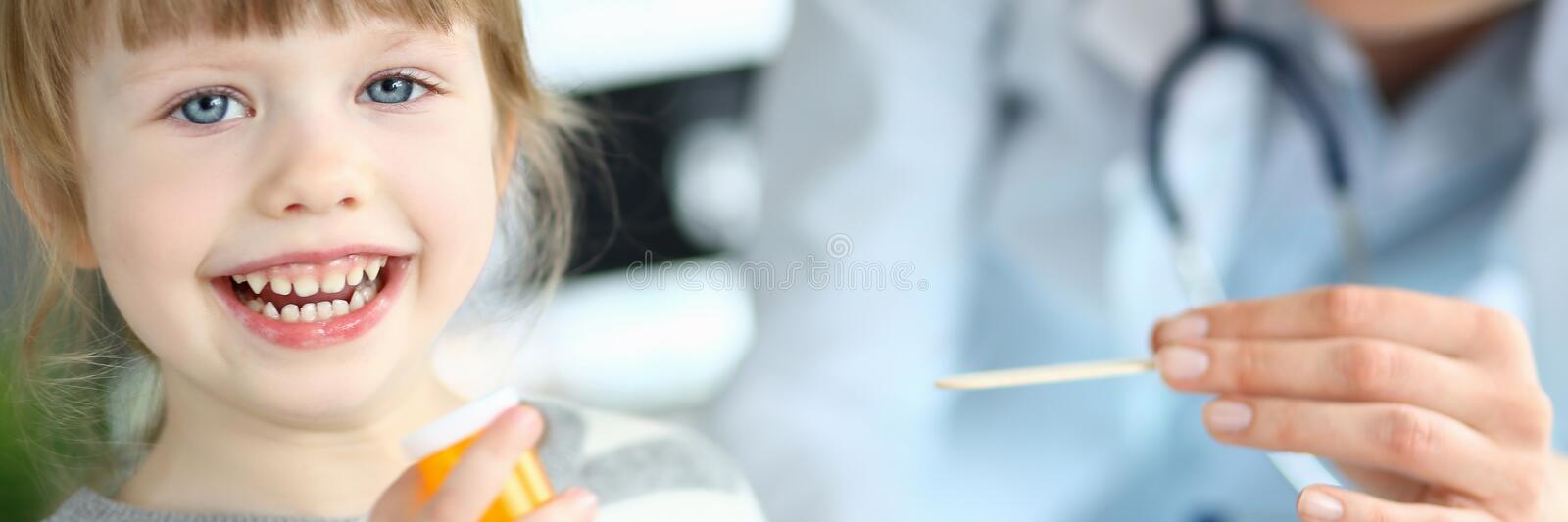 Cute smiling happy little girl hold in hand bottle of tablets at doctor office royalty free stock photo