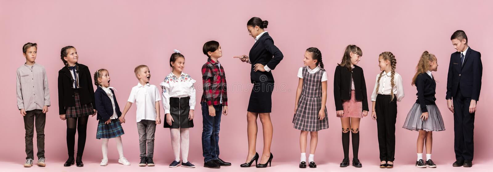 Cute stylish children on pink studio background. The beautiful teen girls and boy standing together. Cute smiling happy stylish children and female teacher on royalty free stock images