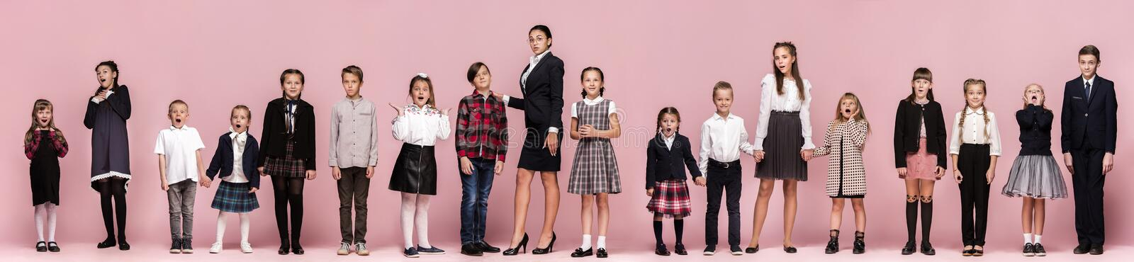 Cute stylish children on pink studio background. The beautiful teen girls and boy standing together. Cute smiling happy stylish children and female teacher on royalty free stock photos
