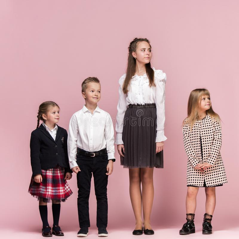 Cute stylish children on pink studio background. The beautiful teen girls and boy standing together royalty free stock images