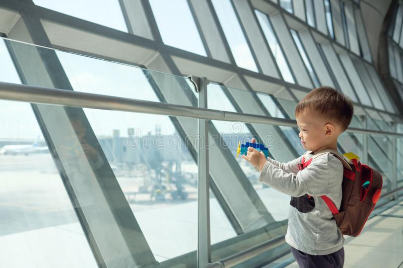 Cute smiling little Asian 2 years old toddler boy child having fun playing with airplane toy while wait for his flight at airport. Little traveler, cute smiling royalty free stock photos