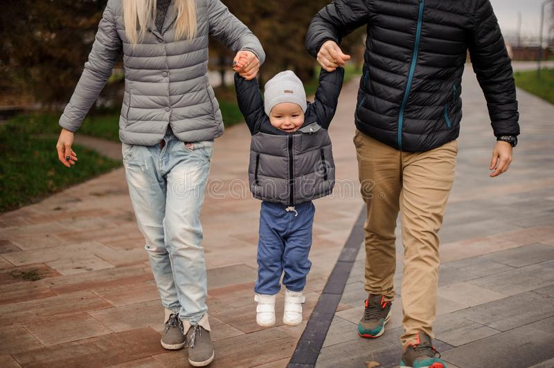 Cute smiling little boy holding parents hands and jumping stock images