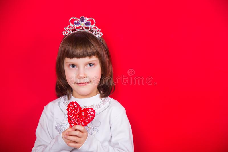 Cute smiling little girl in Christmas costume of snowflake holding wicker heart in studio on red background. New Year banner with empty space stock image