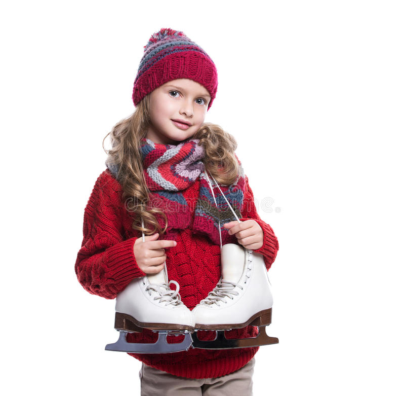 Cute smiling little girl with curly hairstyle wearing knitted sweater, scarf, hat and gloves with skates isolated on white stock photos