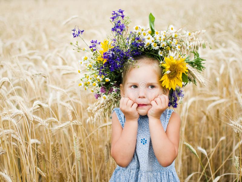 Cute smiling little girl with flower wreath on the meadow at the farm. Portrait of adorable small kid outdoors. stock photos