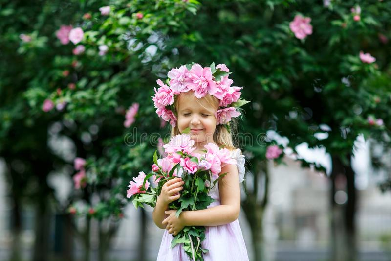 Cute smiling little girl with flower wreath on the park. Portrait of adorable small kid outdoors. Midsummer. Earth Day royalty free stock image