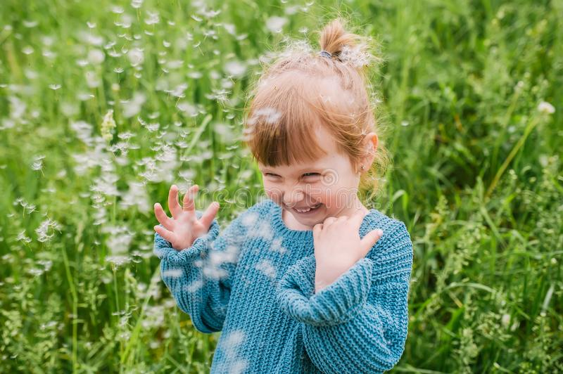 Cute smiling little girl is in grass on the meadow in summer day. Concept of the happy family stock photos