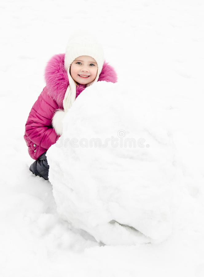 Cute smiling little girl makes snowman in winter day royalty free stock images
