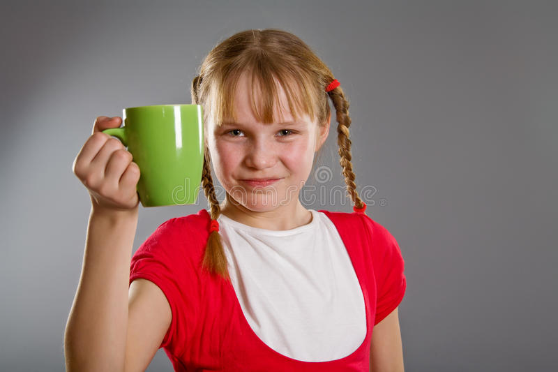 Cute smiling little girl with a mug royalty free stock images