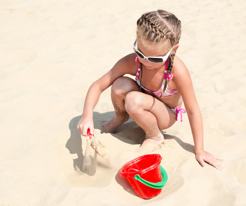 Cute smiling little girl playing on beach royalty free stock photo