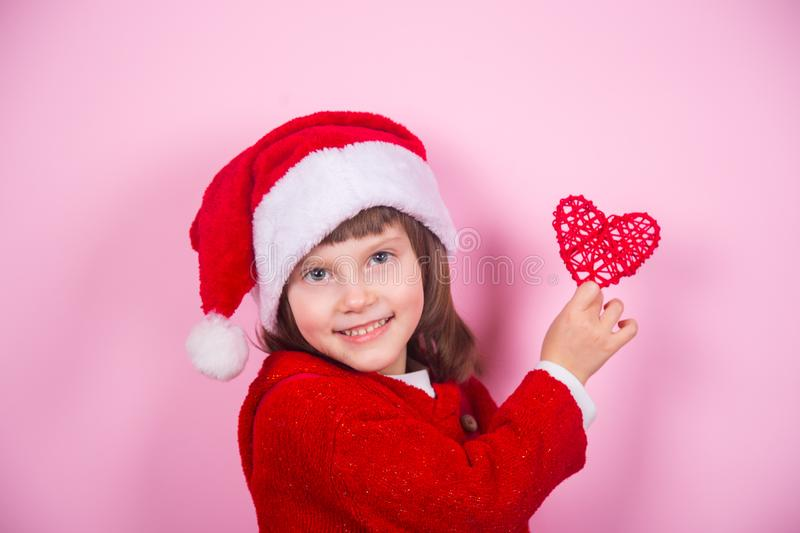 Cute smiling little girl in Santa hat and Christmas costume holding red heart in studio on pink background. New Year banner with empty space royalty free stock photos