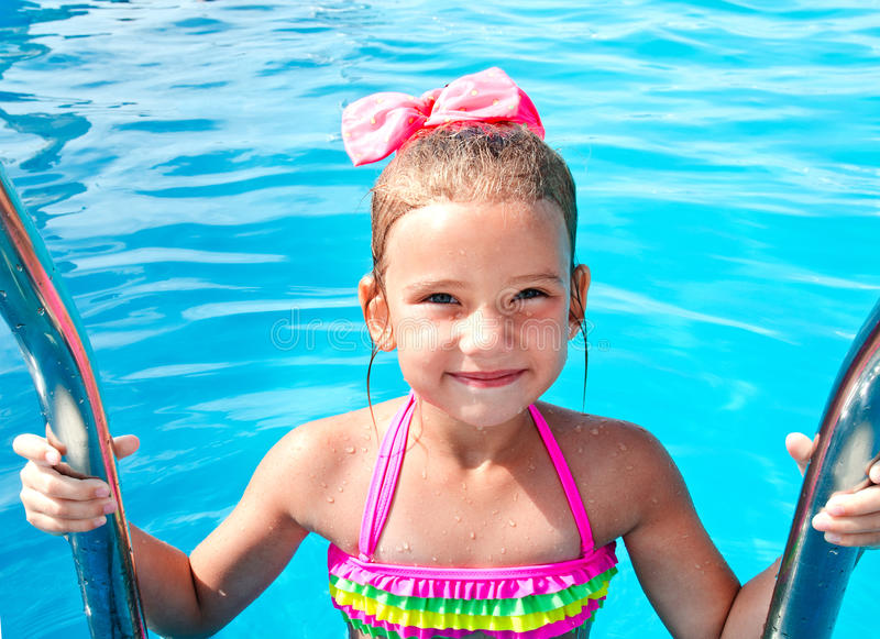 Cute smiling little girl in swimming pool royalty free stock image