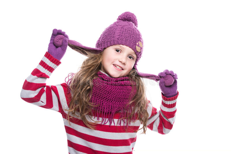 Cute smiling little girl wearing purple knitted scarf, hat and gloves on white background. Winter clothes. stock photos