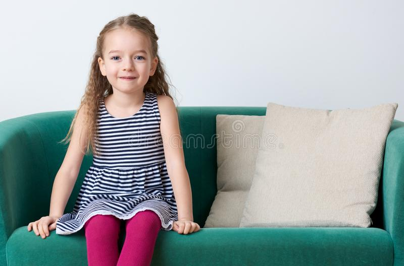 Cute smiling preschooler girl wearing stripy navy blue dress sitting on a couch. royalty free stock photos
