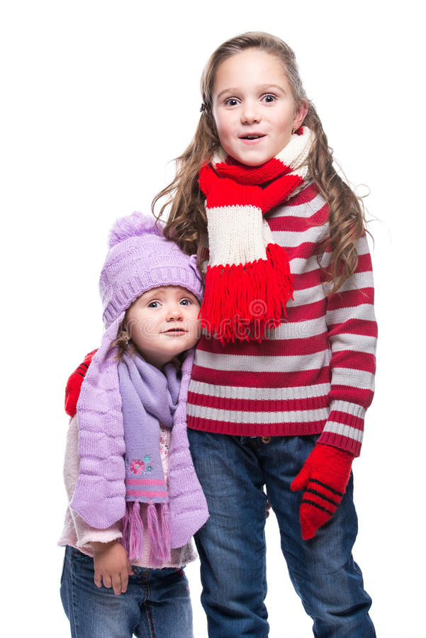 Cute smiling sisters wearing colorful knitted sweater, scarf, hat and gloves isolated on white background. Winter clothes. stock images