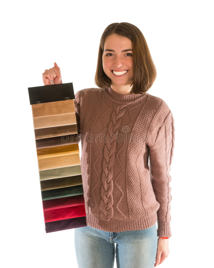 Cute smiling woman in sweater holding fabric swatches. Isolated on white background stock image