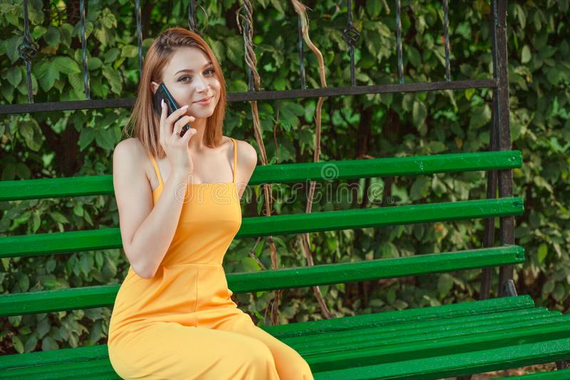 Woman talking by phone while sitting on a bench outside stock images
