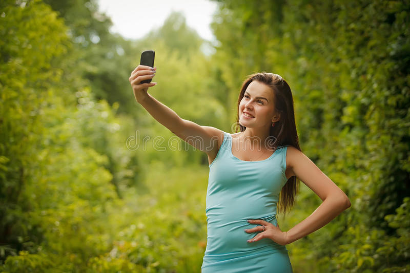 Cute smiling young Caucasian teenage girl taking a selfie outdoors on sunny summer day stock image